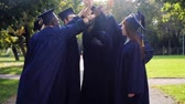 akademický : happy students in mortar boards making high five Dostupné videozáznamy