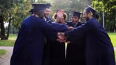 roucho : happy students in mortar boards with hands on top