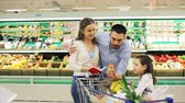 alho : family with food in shopping cart at grocery store