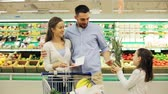 parenthood : family with food in shopping cart at grocery store