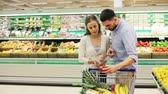kupující : couple with food in shopping cart at grocery store