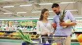 list : couple with food in shopping cart at grocery store
