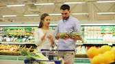writing : couple with food in shopping cart at grocery store