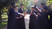 graduating : happy students in mortar boards with diplomas