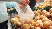 рынок : woman putting onion to bag at grocery store