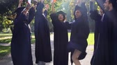 akademický : happy students in mortar boards with diplomas