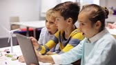 věda : kids with tablet pc programming at robotics school