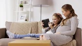 parenthood : pregnant woman and girl with tablet pc at home