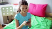 гаджет : smiling girl texting on smartphone at home