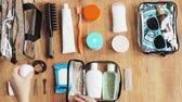 topo : hands packing cosmetic bag with stuff for travel