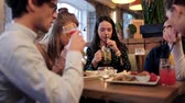 internacional : happy friends eating and drinking at bar or cafe Stock Footage