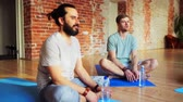 instrutor : men with water resting on yoga mats in gym Stock Footage