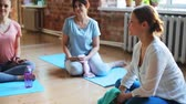 instrutor : group of women resting on yoga mats in gym