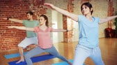 família : group of people making yoga exercises in gym
