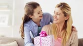 família : happy girl giving present to mother at home