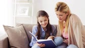parentalidade : happy girl with mother reading book at home Stock Footage