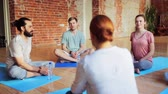 instrutor : group of people resting on yoga mats in gym