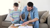 parentalidade : father and little son with crayons drawing at home Stock Footage