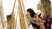 quadro : students with easels painting at art school