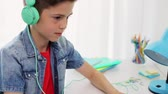 play video game : boy in headphones playing video game on laptop