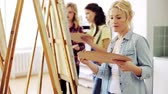 artists canvas : students with easels painting at art school