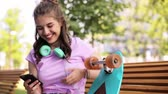 enforcamento : happy teenage girl with smartphone and longboard