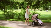 pram : happy mother with baby in stroller walking at park Stock Footage