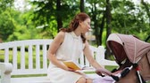 pram : mother with baby in stroller reading book at park