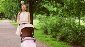 pram : mother with baby in stroller at summer park Stock Footage