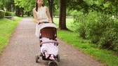 pram : mother with baby in stroller walking at park