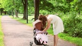 pram : mother with baby girl in stroller at summer park Stock Footage