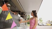 tecido : young woman ordering vegan wrap at food truck