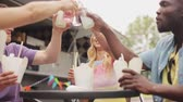 friends clinking bottles of drinks at food truck