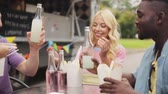 pauzinho : friends clinking bottles of drinks at food truck