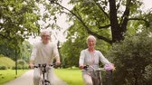 bicyklista : happy senior couple riding bicycles at summer park