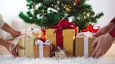 montão : hands putting gift boxes under christmas tree