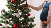 gravidez : pregnant woman decorating christmas tree at home