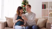 man and pregnant woman taking selfie at christmas