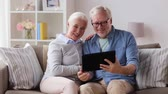 размахивание : senior couple having video chat on tablet pc Стоковые видеозаписи