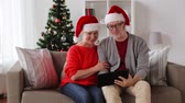 hi : happy senior couple with tablet pc at christmas Stock Footage