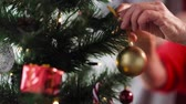 ouro : senior woman hands decorating christmas tree