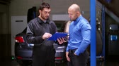 garagem : mechanic and customer shaking hands at car service