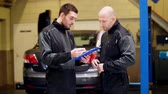 garagem : auto mechanics with clipboard talking at car shop
