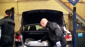 auto : mechanics taking tires out of car trunk at service Stock Footage