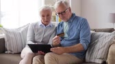 plástico : happy senior couple with tablet pc and credit card
