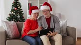 hat : happy senior couple with tablet pc at christmas Stock Footage