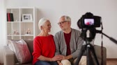 kayıtlar : happy senior couple with camera recording video