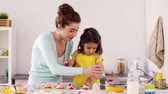 borrifar : mother and daughter cooking cupcakes at home