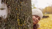 jardim de infância : beautiful little girl hiding behind tree in autumn Stock Footage