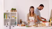 pieczarka : happy couple cooking food and having fun at home